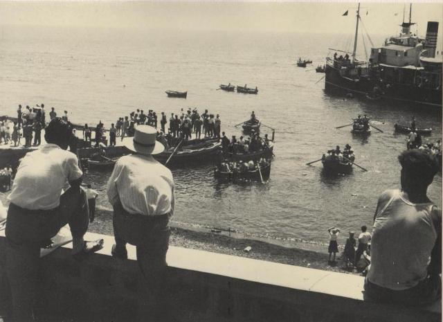 La gente assiste allo sbarco dal vaporetto con le barche dei pescatori