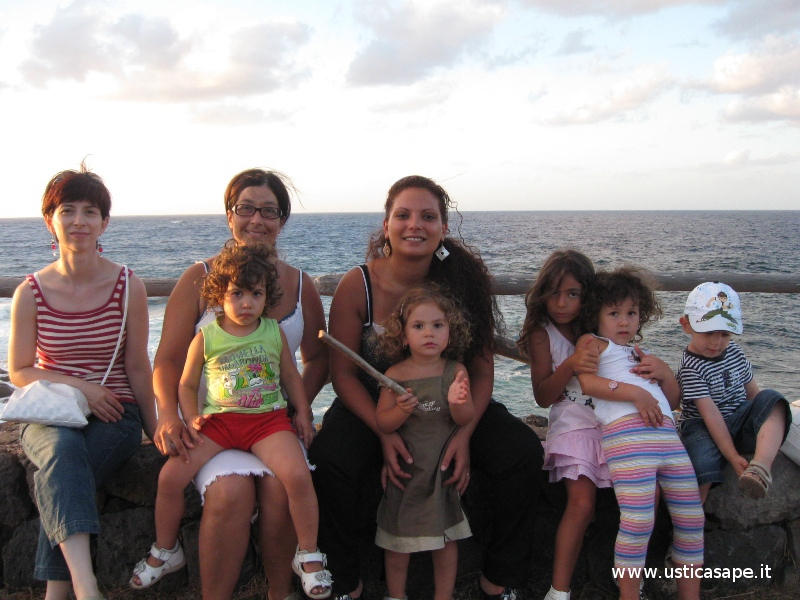 mamme e figli seduti in riva al mare