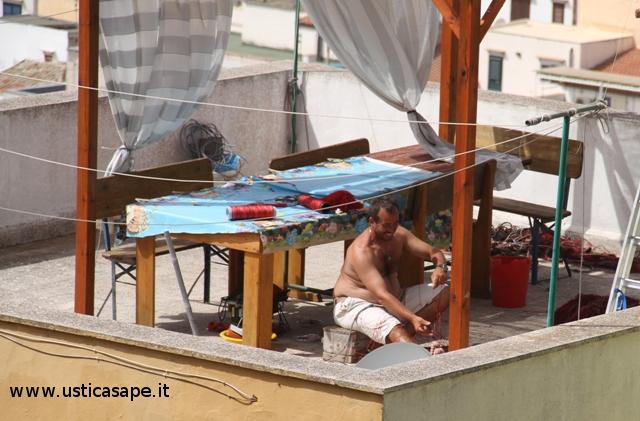 Pescatore professionista prepara reti speciali sul tetto di casa lontano da occhi indiscreti