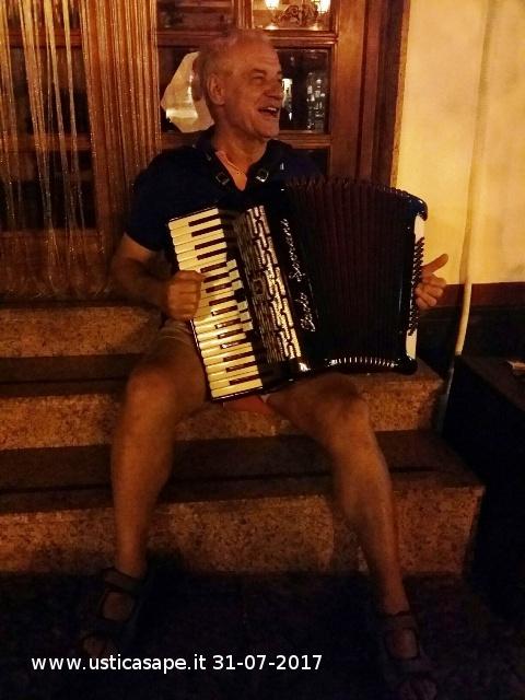 Giovanni con la sua fisarmonica allieta la piazza   di Ustica