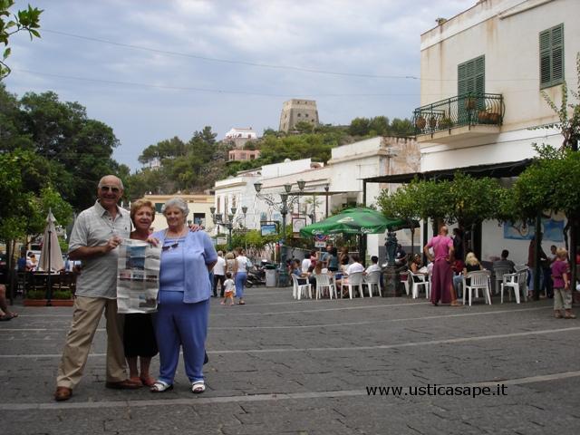 Ustica piazza, Turisti mostrano giornale per concorso