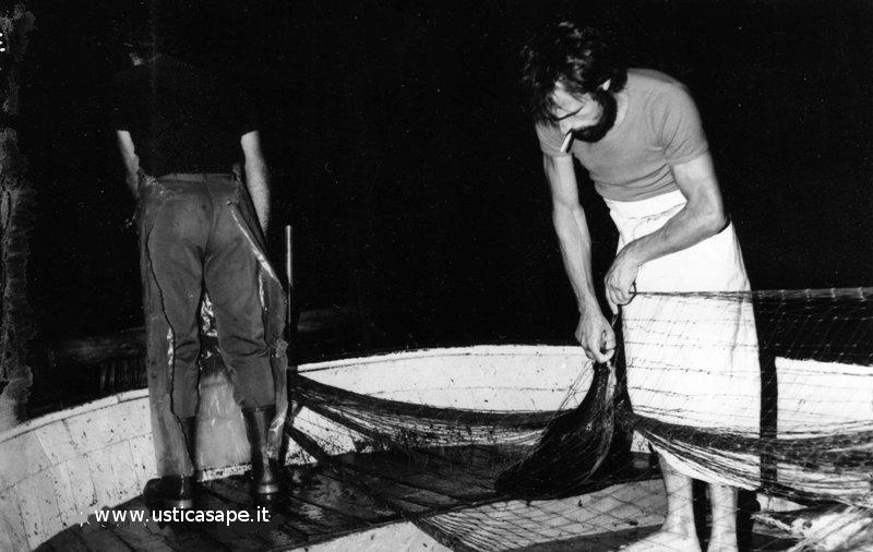 mentre il pescatore tira la rete l'altro smaglia il pesce