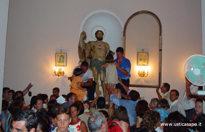 Ustica, dopo la processione ai bambini, per devozione, si fa baciare il santo